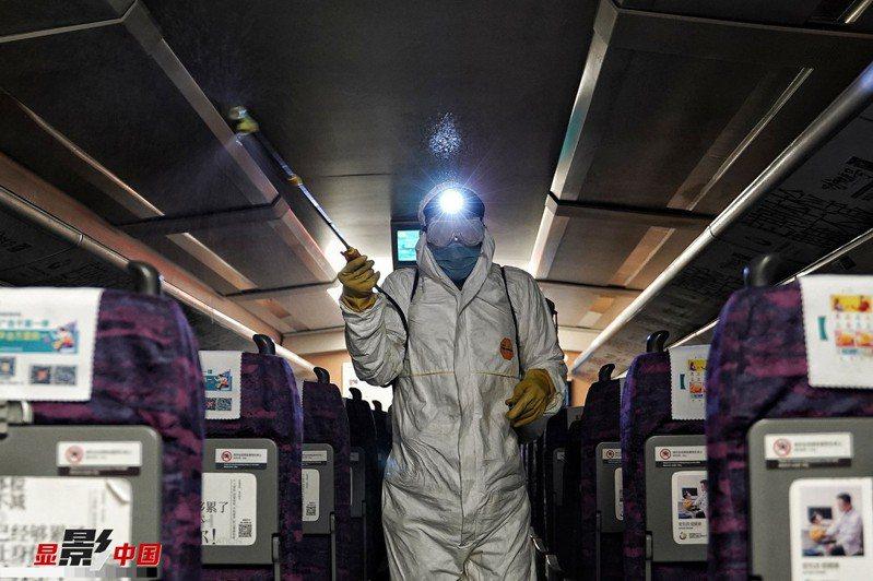 武漢肺炎重創大陸運輸業。圖為中國鐵路南寧局集團有限公司清潔人員,正在為列車車廂進行消毒。(新華網)