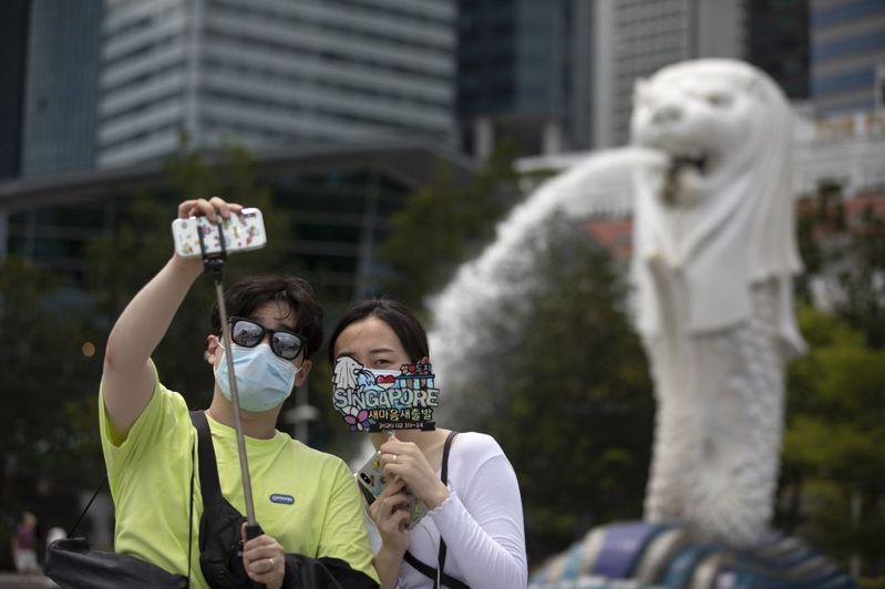 觀光客戴上口罩遊獅城。武漢肺炎疫情導致大陸遊客大減,已衝擊亞洲各國觀光業。歐新社