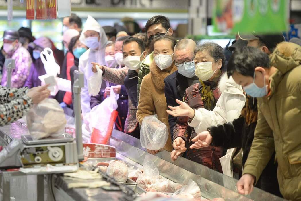 大陸武漢是這次新冠肺炎疫情發源地。圖為許多戴口罩的民眾在武漢一間超市內排隊購物。...