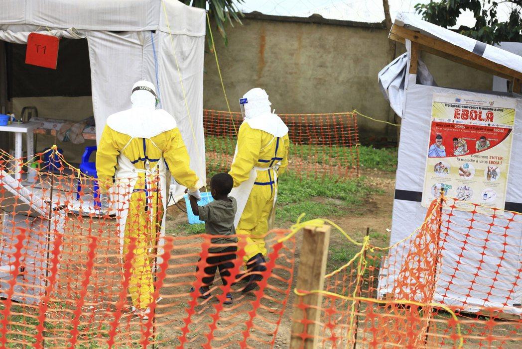 剛果東部2018年傳出伊波拉疫情,兩名醫護人員牽著一個疑似染病的孩童就醫。 (美...