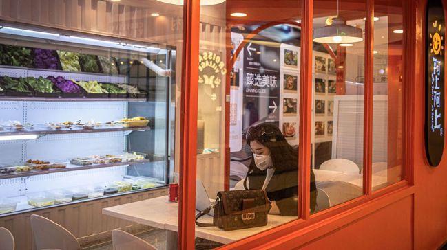 女子戴口罩獨坐在北京一座購物中心的咖啡廳。受武漢肺炎疫情影響,整座商場空蕩蕩的,...