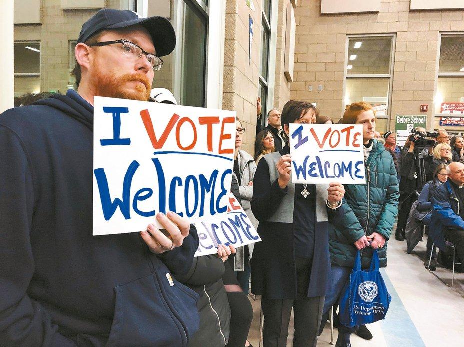 圖為美國北達科他州民眾舉牌支持繼續接收難民。 美聯社