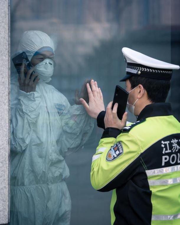 醫警夫妻因在前線抗疫已經十幾天沒有見到對方,兩人隔著玻璃打電話,伸手想觸摸卻碰不到對方。圖擷自觀察者