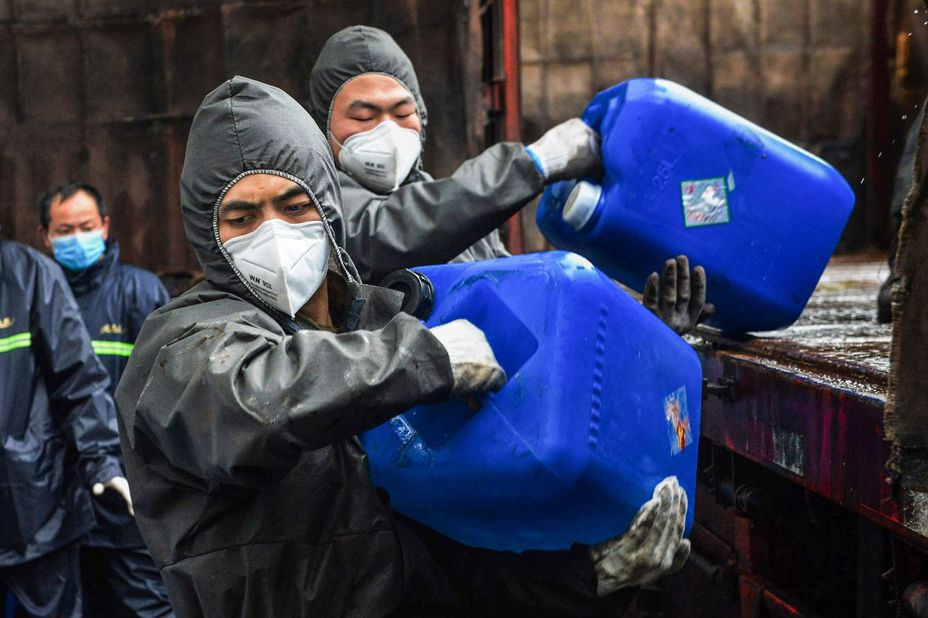 紐時報導,由於中國確診人數計算方式前後不一,世人至今難以理解新冠肺炎疫情究竟嚴重到什麼程度。圖為湖北省孝感市郊12日有軍警穿著防護衣,運送消毒劑。法新社