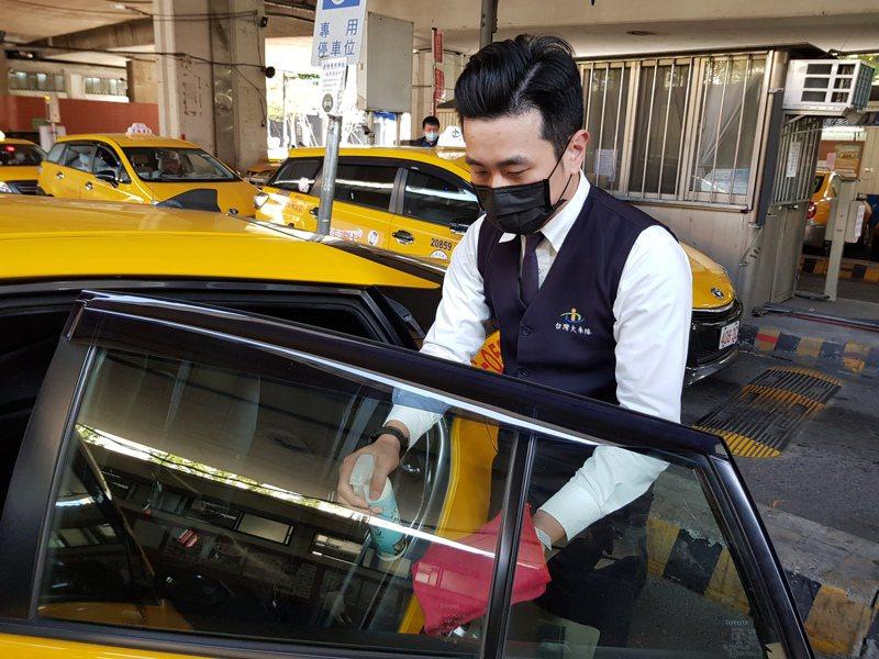 有北市計程車駕駛指出,現在載客機會變少,生意大概少2、3成,每天也要趁載客空檔拿車隊配發的酒精消毒車內扶手、門把等處。記者翁浩然/攝影