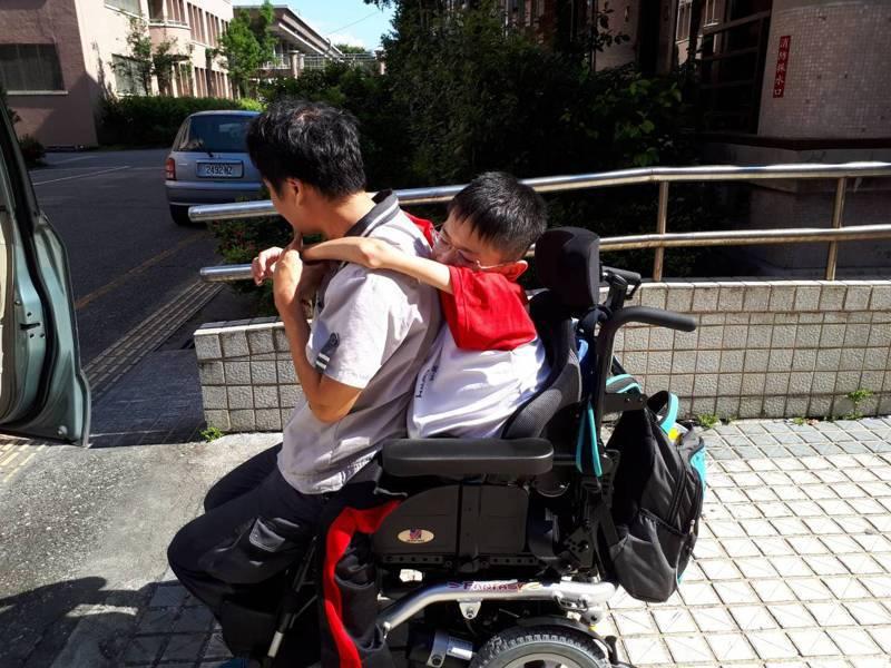 梁爸爸辛苦的開車接送,一到校先拿出輪椅,再小心地讓梁匡豐坐在輪椅上。圖/光復商工提供