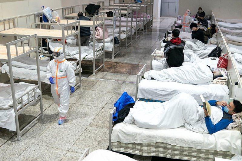 穿著防護服的醫護人員在照顧冠狀病毒患者。 圖/路透