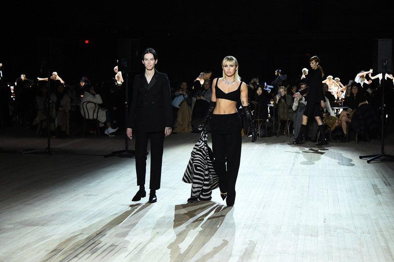 麥莉穿著黑色小可愛搭配黑色寬管褲走上伸展台大秀腹肌,也在懷舊的氛圍中展現了現代女性的自信與霸氣。圖/Marc Jacobs提供