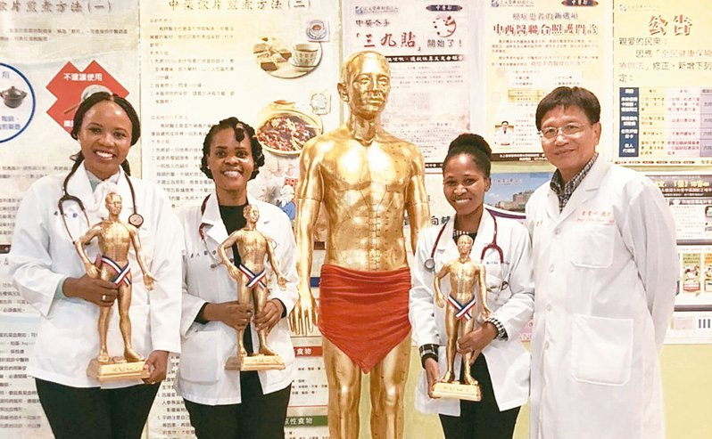 義守大學學士後中醫學系教授蔡金川(右一)贈送外籍學生「小金人」,他們是中醫院常見的十八銅人像。 圖/義守大學提供