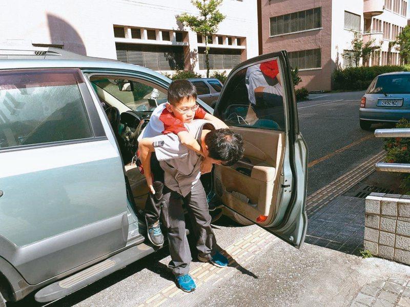 梁爸爸每天開車接送梁匡豐上下課,小心背他下車。 圖/光復商工提供