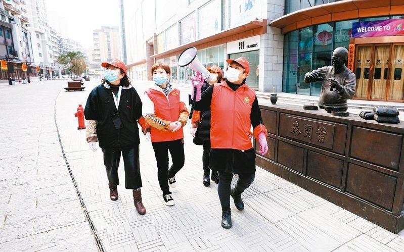 湖北武漢社區志願小組,以擴音器沿街向居民喊話,提醒新冠肺炎持續升溫期應注意事項。 新華社