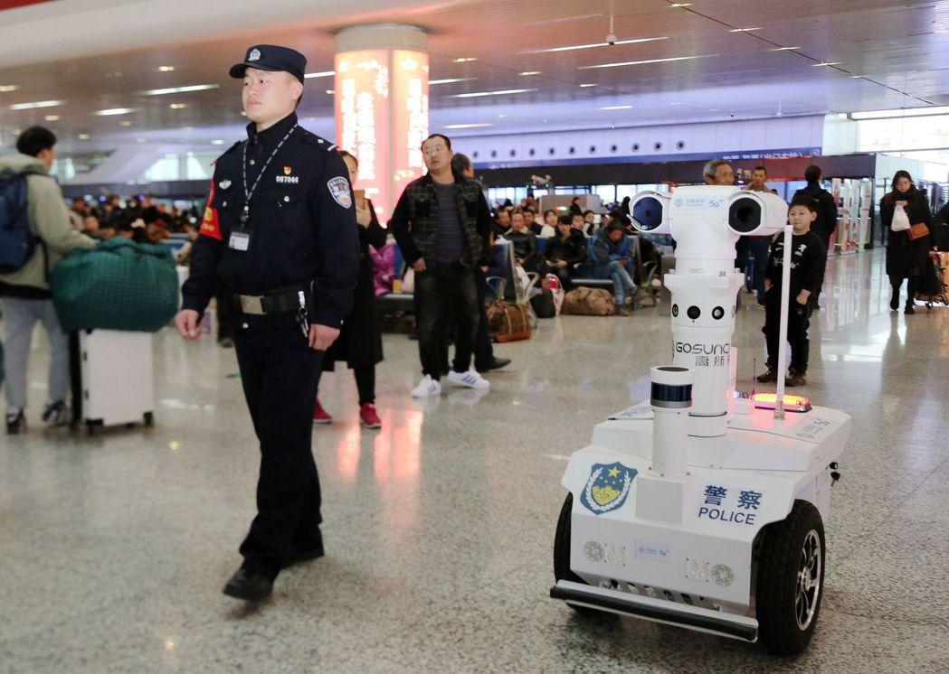 圖為今年1月,中國大陸民警和搭載5G、AI技術的機器人共同巡邏車站。中新社