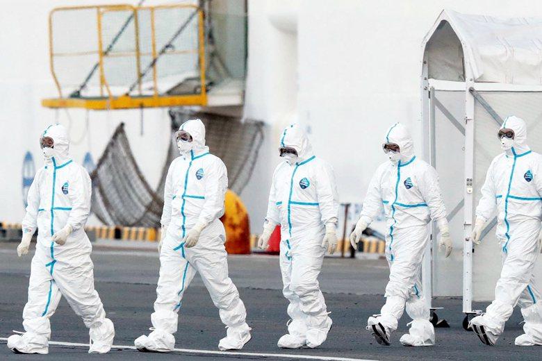 鑽石公主號郵輪海上隔離期間,檢疫人員穿著全套防護衣上船檢疫。 圖/美聯社