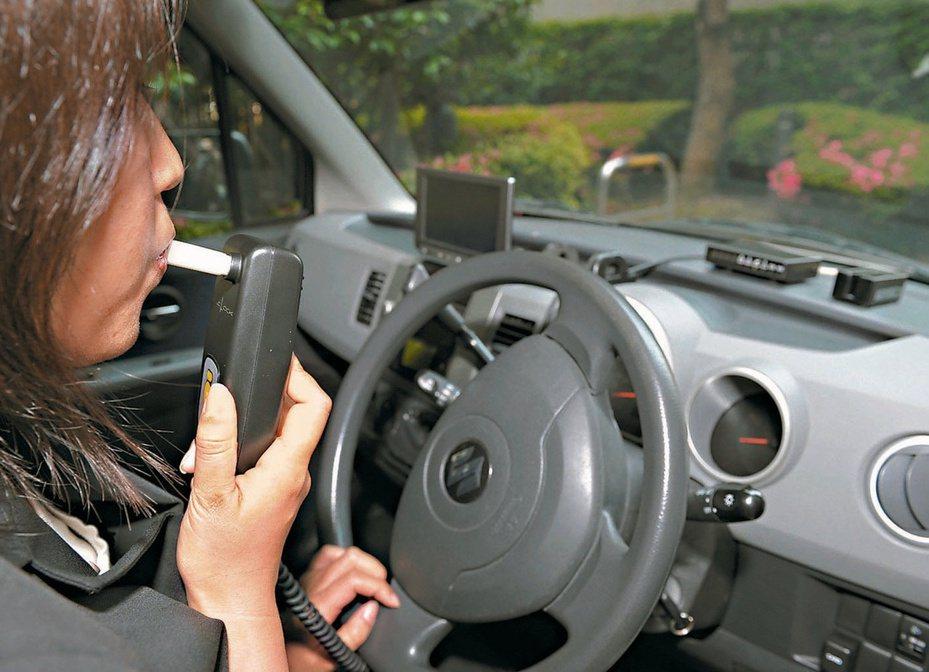 防止酒駕累犯肇事的酒精鎖新制,3月上路。圖為日本東海電子員工示範先呼氣酒測才能發動汽車的酒精鎖。法新社