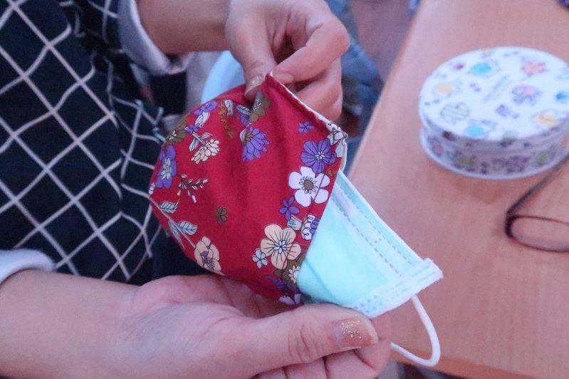 在布口罩中套上防疫口罩,這樣可以只清洗外層布口罩,裡層的防疫口罩就可以多使用幾次。記者徐如宜/攝影
