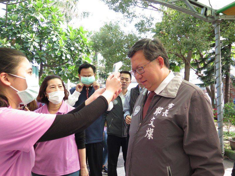 桃園市長鄭文燦今天到八德區旭登護理之家視察,進入前先量額溫。記者張裕珍/攝影