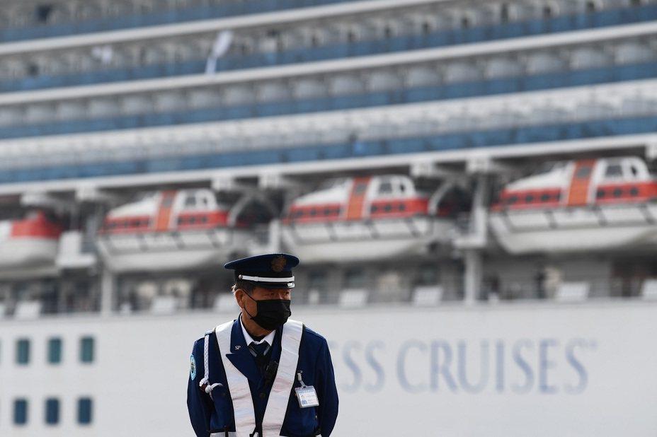日本一名警衛14日站在停靠於橫濱港的鑽石公主號遊輪附近。日本沖繩縣一位60多歲的女性計程車司機確認感染新冠肺炎,據指鑽石公主號郵輪1日停靠那霸港時,她曾載著4名下船的中國觀光客前去遊覽。法新社