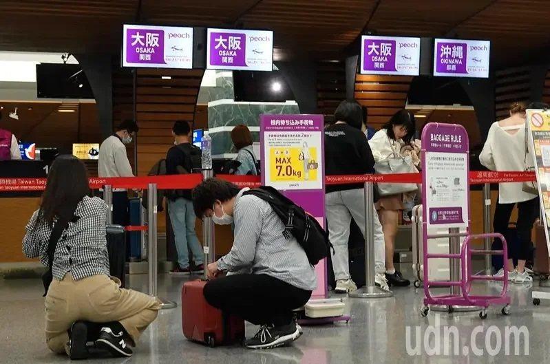 中央流行疫情指揮中心宣布即日起提升日本旅遊疫情建議至第一級注意(Watch),昨天傍晚仍有不少民眾帶著口罩在桃機搭機前往日本。記者鄭超文/攝影