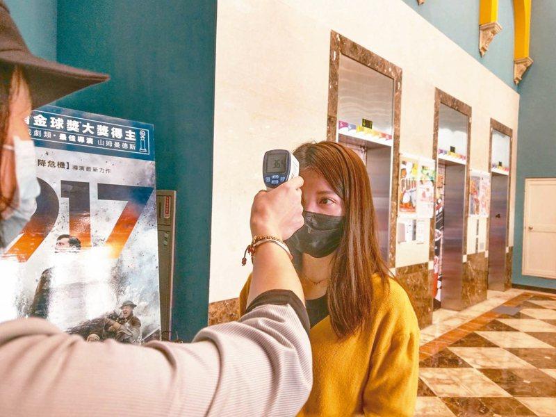 行政院消保處日前派員訪視雙北電影院及KTV場所,建議業者主動於消費者入場前,為其消毒清潔雙手及量測體溫。圖為內湖哈拉影城替觀眾量額溫。 圖/哈拉影城提供