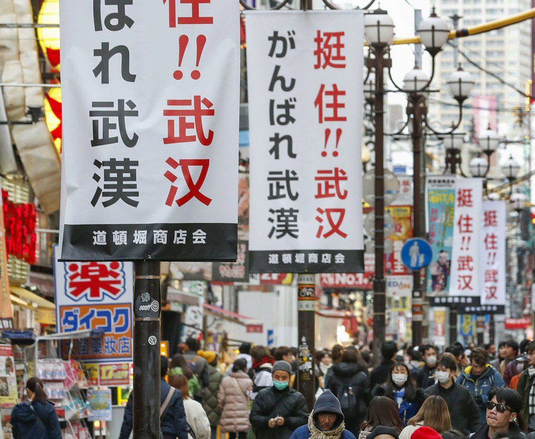 大阪道頓堀商圈的街道上掛滿了中日雙語的「挺住!武漢」標語。 (新華社)