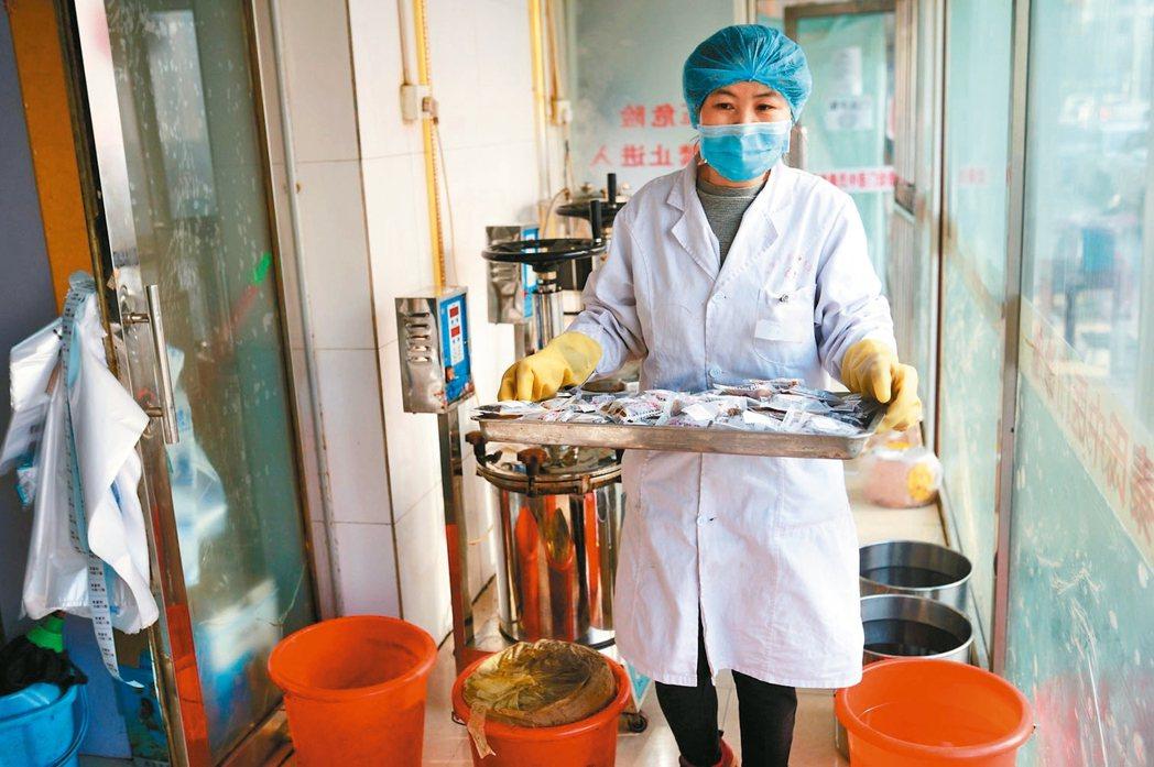 中國大陸開始使用中醫藥治療確診病例。圖為街道轄區診所為居民和工作人員熬製提高抵抗...