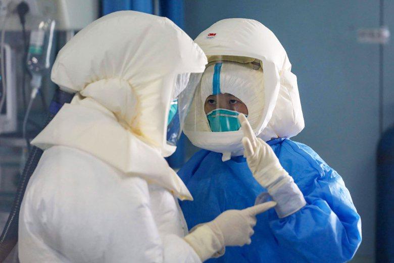 金銀潭醫院負壓隔離病房,兩名醫護人員身穿全套防護裝備。 圖/美聯社