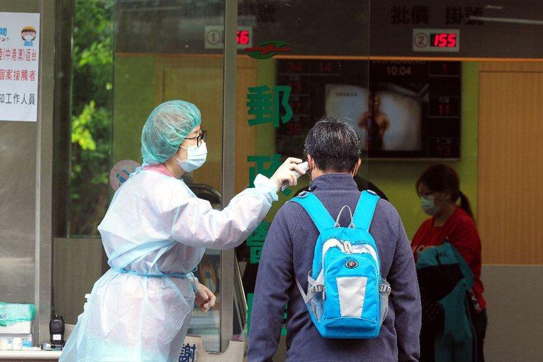 2月6日,一名醫護人員為進入醫院的民眾量體溫。 圖/歐新社