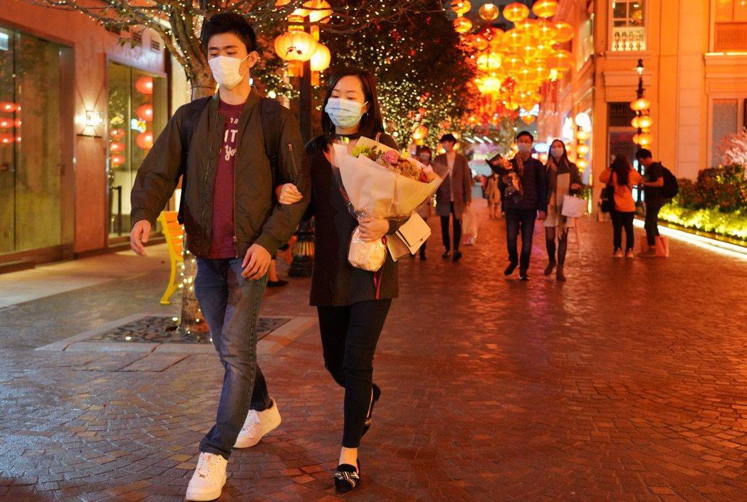 香港受新冠肺炎疫情影響,今年情人節,情侶都戴著口罩上街。 (香港中通社)