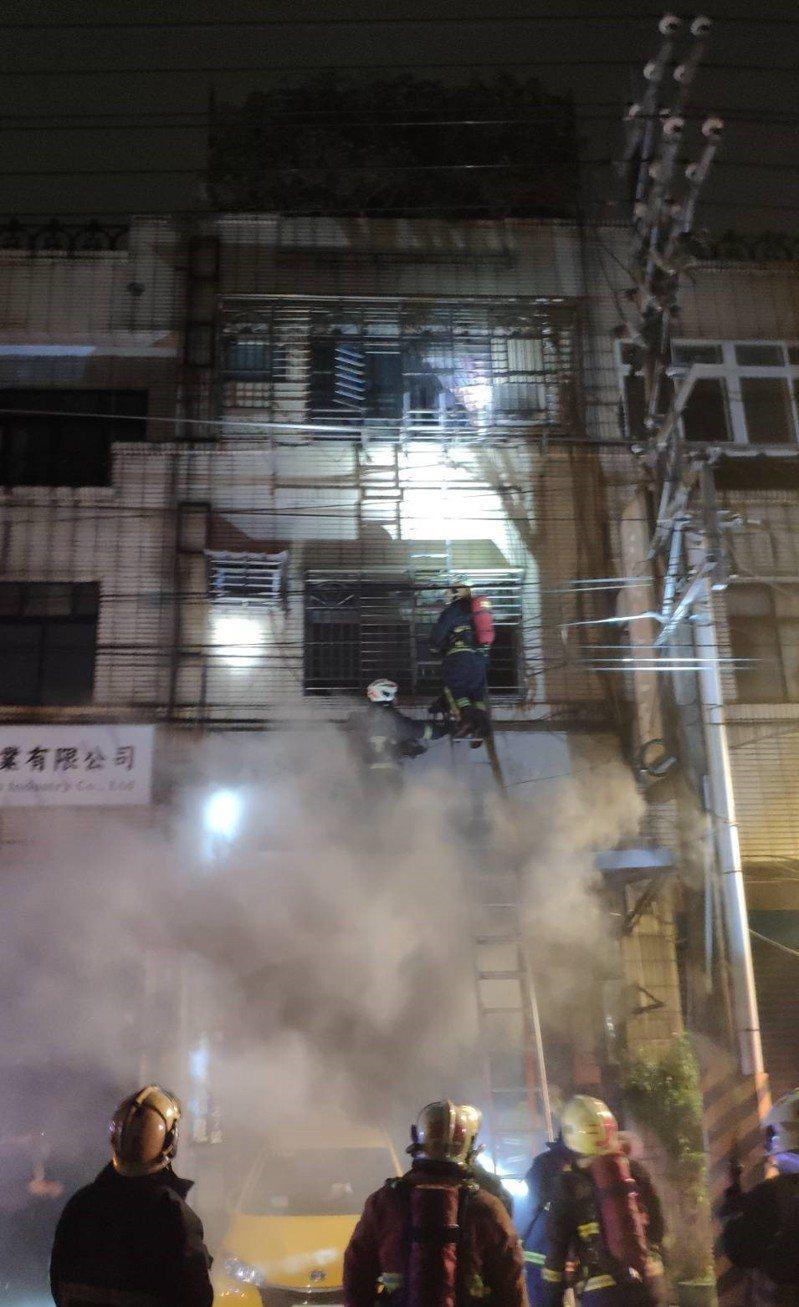 消防員一邊滅火,同時進行搶救,並架設架梯並壞鐵窗將拯救位在2樓前陽台的女子。記者陳弘逸/翻攝