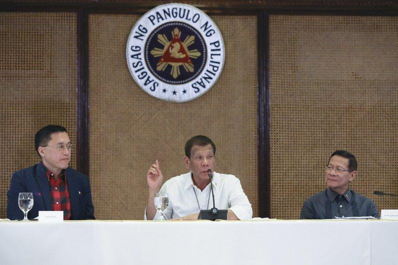 菲律賓總統杜特蒂(中)原本禁止台灣旅客入境的政策,14日又決定解除對台灣旅行禁令,以免15萬在台菲國移工受累。(歐新社)