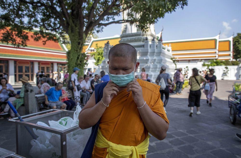 泰國數百年古剎臥佛寺因為新冠肺炎疫情爆發,遊客大量減少。一名臥佛寺僧侶戴上口罩避...