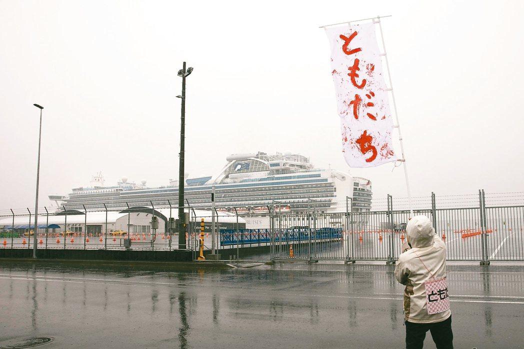 揮舞〝朋友〞旗幟一名男子在郵輪附近揮舞旗幟,上面用日本寫著「朋友」。 美聯社