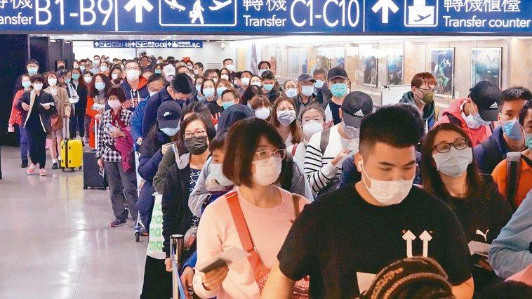 新冠肺炎疫情升溫,入境旅客因須填寫健康聲明卡,在篩檢站前大排長龍。圖/聯合報系資...