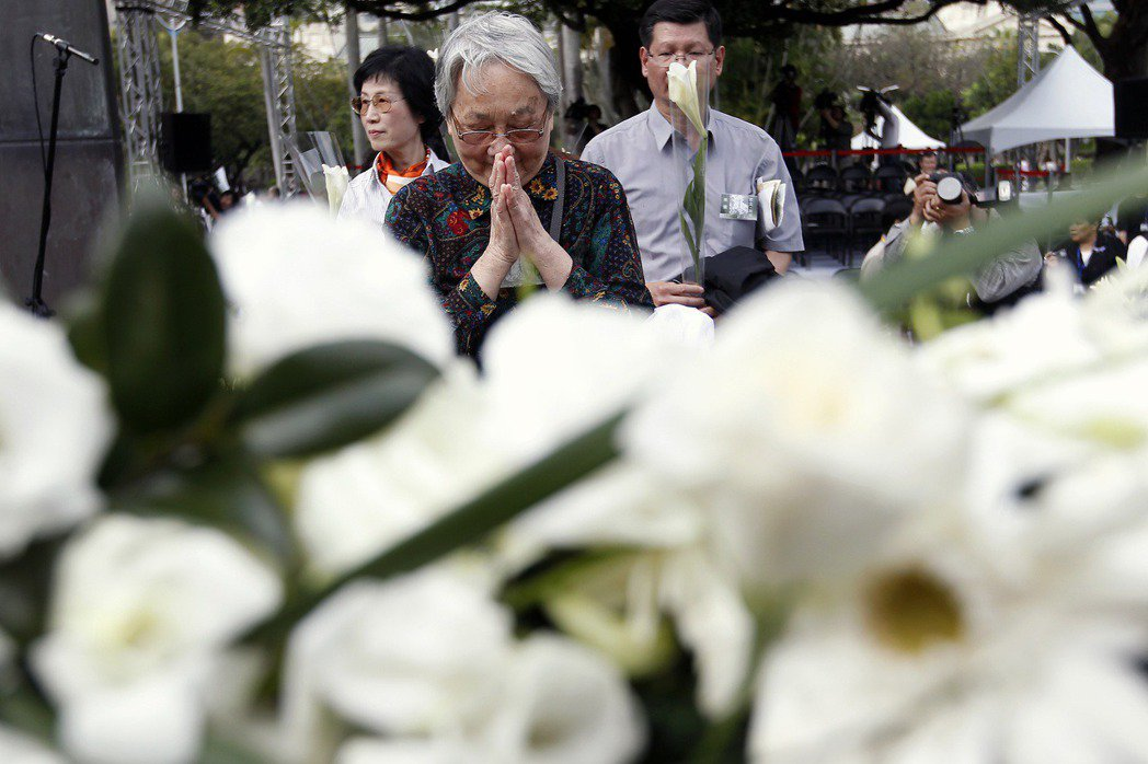 民眾在二二八事件紀念活動上獻花及禱告。攝於2013年。 圖/路透社
