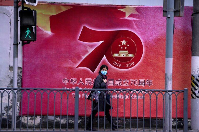 2月14日,上海民眾戴上口罩防疫。 圖/路透社