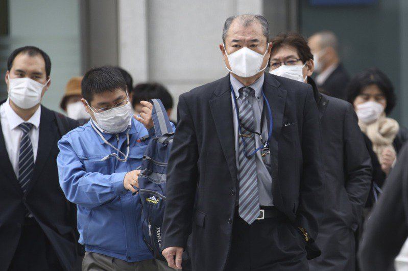 日本東京街頭戴著口罩預防被病毒傳染的人們。美聯社