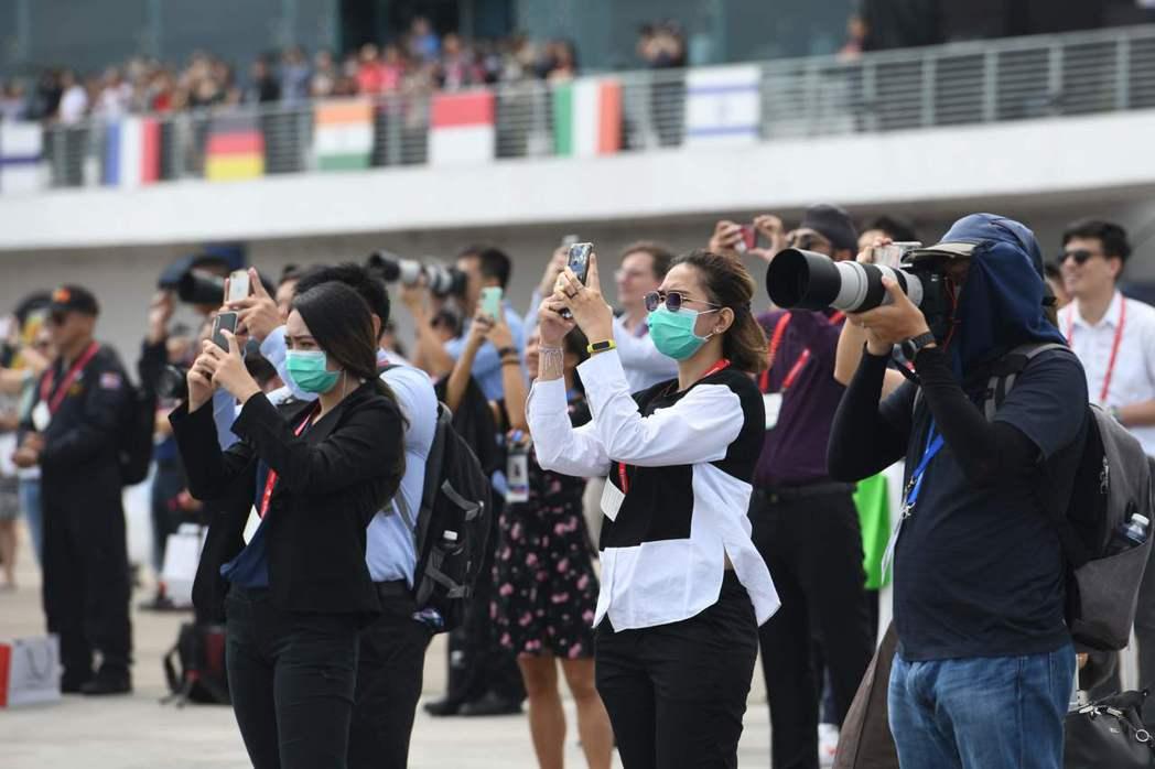 一些遊客13日戴著口罩觀看新加坡航空展的飛行表演。法新社