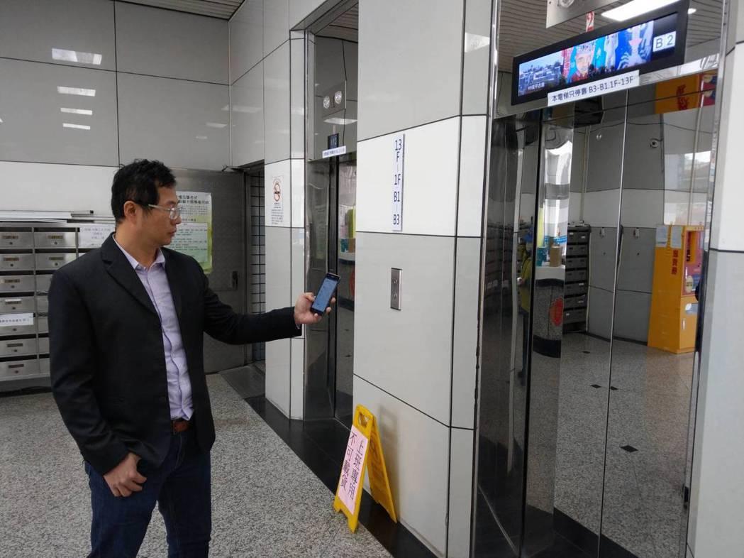 盛大電梯總經理許弼凱透過手機App呼叫電梯,展示「iLift智慧電梯IoT」。莊...