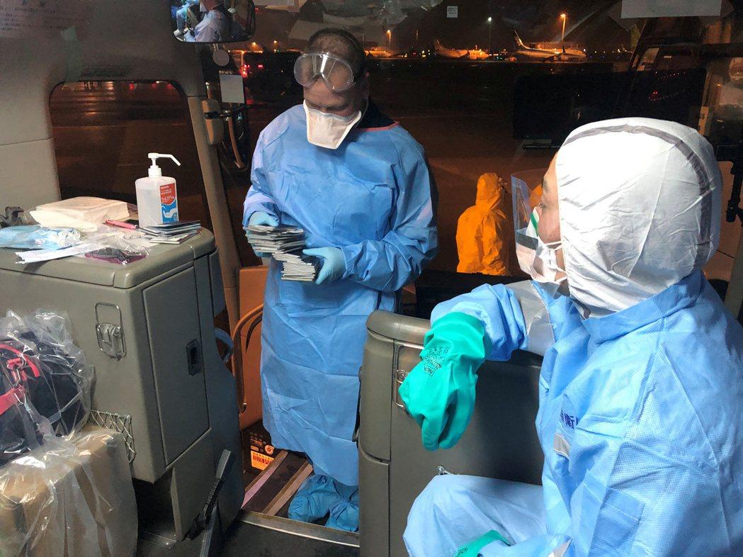 日本厚勞省人員穿著防護衣護送從鑽石公主郵輪號離開,要搭專機回美國的美國公民。路透