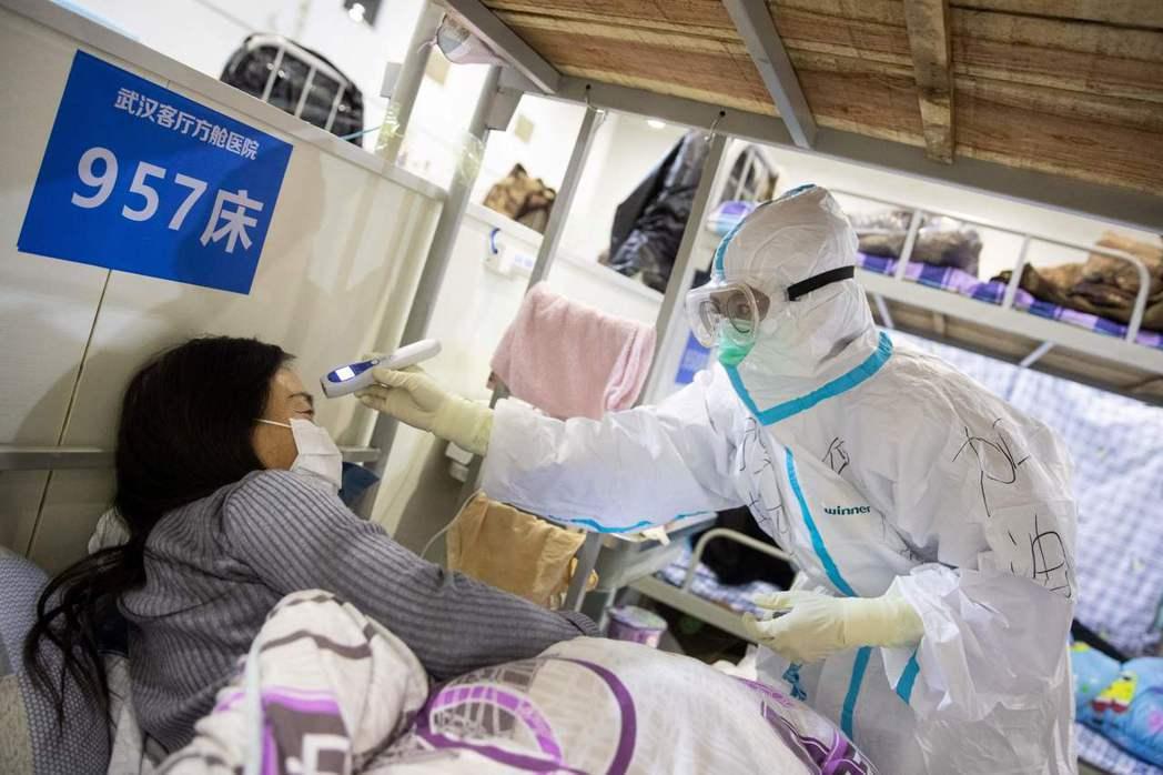 武漢一家醫院的醫護人員17日為病患量體溫。法新社