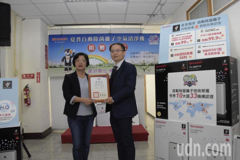 台灣夏普公司總經理張凱傑(左)捐贈100台空氣清淨機給彰化縣政府,由縣長王惠美代表接受。記者劉明岩/攝影