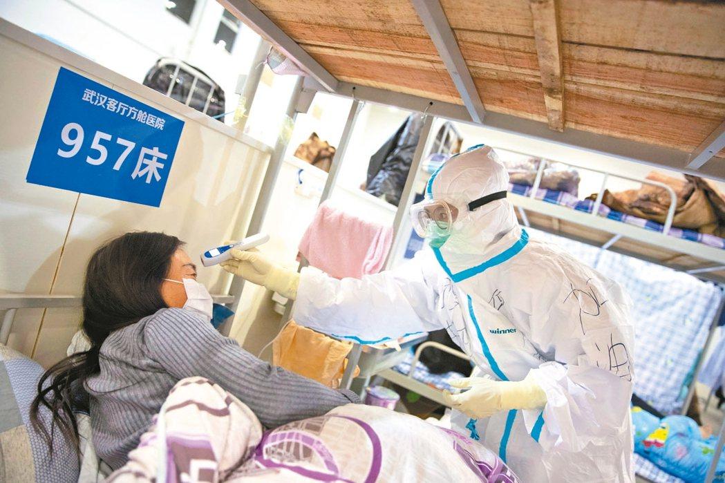 身穿防護服的醫務人員在武漢方艙臨時醫院為新冠肺炎患者測量體溫。 歐新社