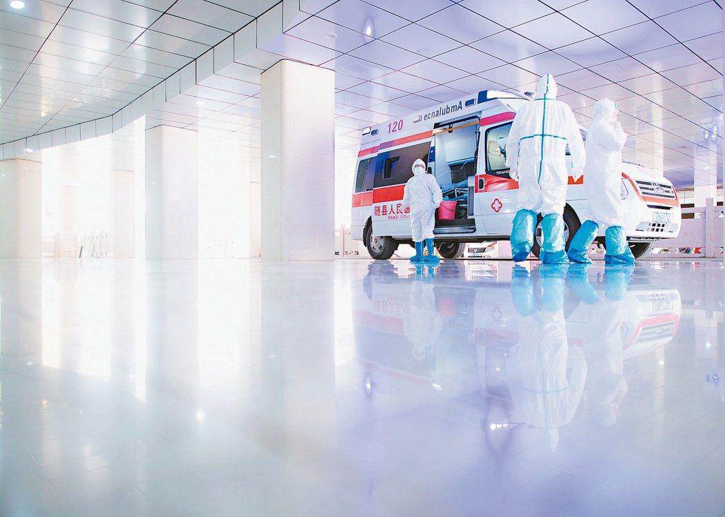 湖北新冠病毒疫情持續擴散。圖為醫護人員準備從救護車裡接收一名疑似染病患者。( 新...