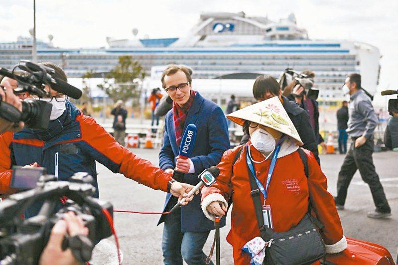 各國乘客陸續離開 鑽石公主號郵輪乘客今天隔離期滿,上午首批約500名新冠肺炎篩檢陰性的乘客陸續下船,媒體試圖訪問一名下船的鑽石公主號郵輪乘客(右)。法新社