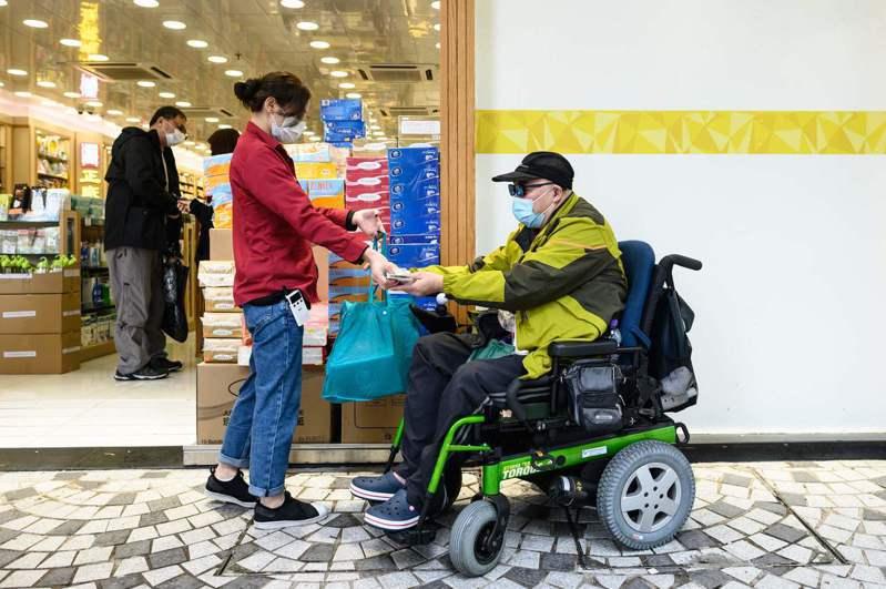 買口罩是香港身障人士不可能的任務,圖為身障的甄先生買衛生紙。法新社
