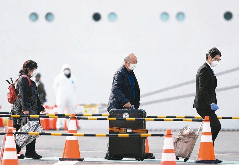橫濱港的鑽石公主號遊輪旅客下船時,一名駕駛員幫助他們拿行李。 路透社