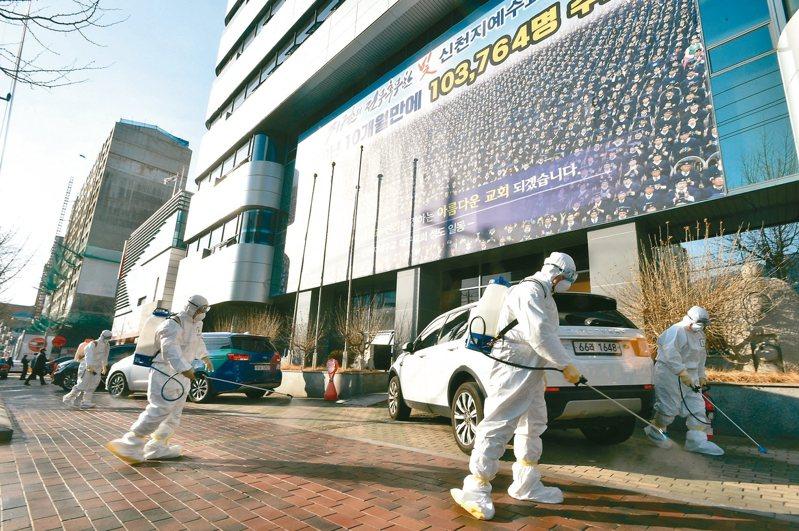 南韓新冠肺炎疫情擴大,進入社區傳染階段。圖為第31號確診病例做禮拜的教堂前街道正進行消毒工作。 路透