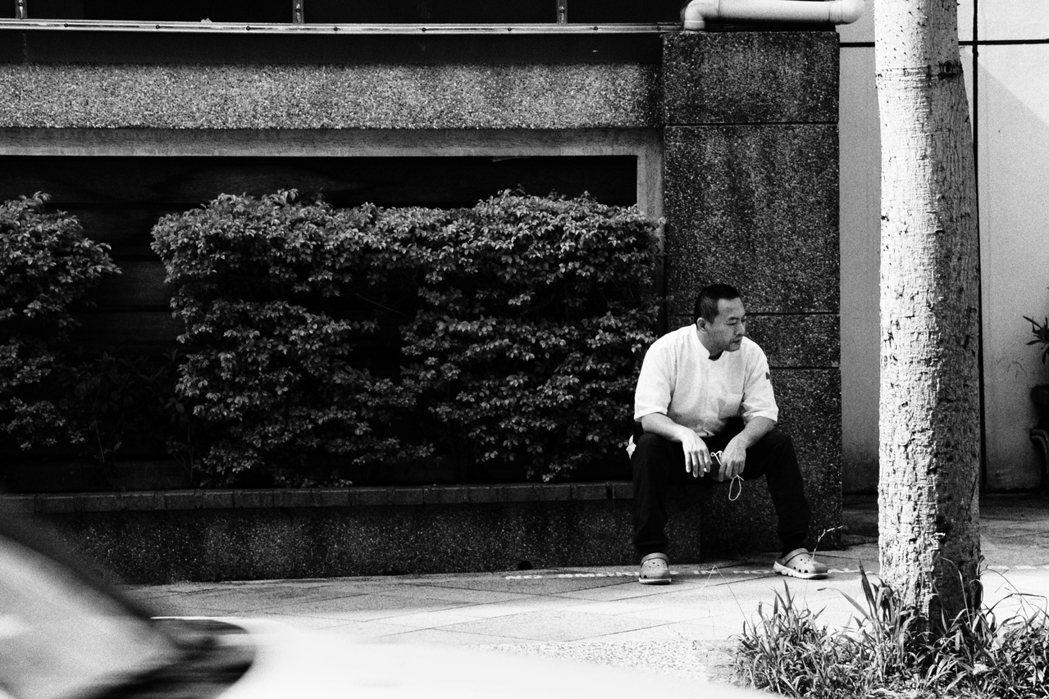 臺北市聯合醫院仁愛院區外一位民眾正在吸菸,腳下告示寫著「進入院區禁止吸菸」。 (...