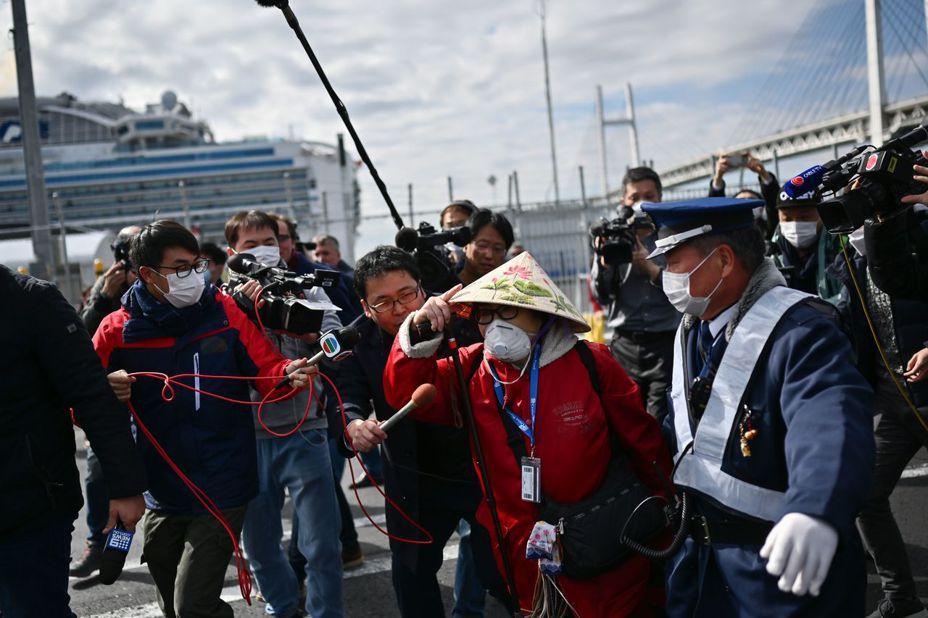 結束隔離的「鑽石公主號」乘客十九日開始分批下船,一名戴口罩和越南斗笠的乘客快步離去。(法新社)