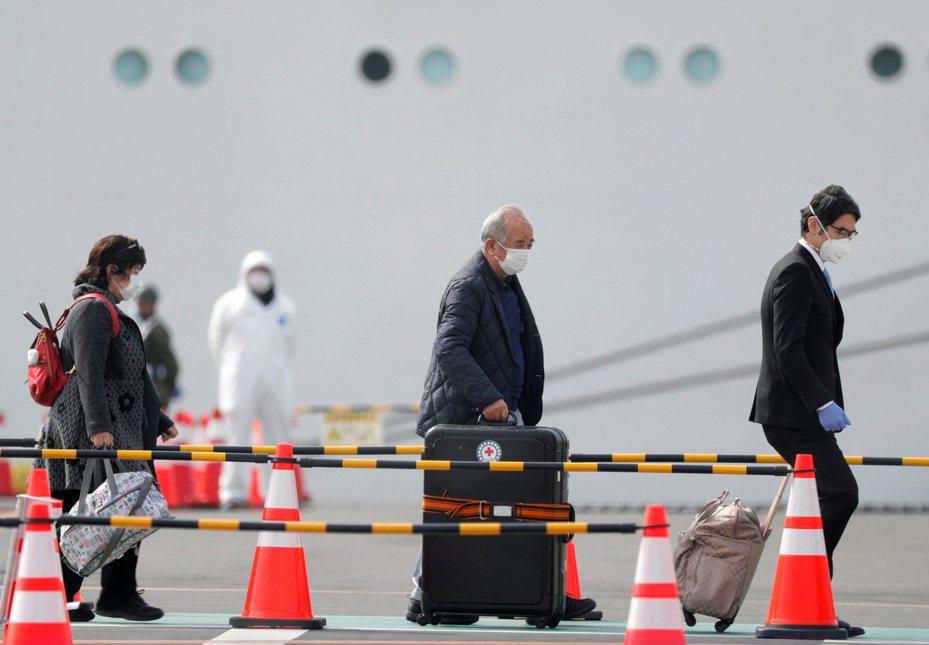 橫濱港的鑽石公主號遊輪旅客下船時,一名駕駛員幫助他們拿行李。路透社